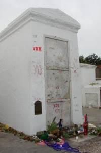 Hrobka Marie Laveau v New Orleans. Její příznivci u ní dodnes nechávají zapálené svíčky a drobné dárky v podobě jídla, pití, parfémů či šperků. Opakující se motiv tří křížků je její symbolickou signaturou. Marie Laveau byla negramotná a na historických dokumentech se namísto jejího podpisu nacházejí právě tři křížky.